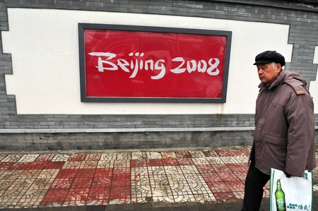 olympic games: BEIJING - MARCH 13:Chinese man walking by a street sign of Beijing 2008 olympic games on March 13 2009 in Beijing China.Beijing hosted  Olympics games from August 8 to 24 2008. Editorial