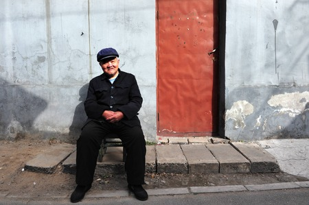 dirty old man: BEIJING - MARCH 12:An old Chinese man sits outside his home in Hutong old neighbourhood on March 12 2009 in Beijing, China.There is around 4,000 Hutongs in Beijing some are hundreds of years old