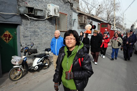 guia de turismo: BEIJING - MARCH 11:A tour guide with tourists visiting a Hutong old neighbourhood on March 11 2009 in Beijing, China.There is around 4,000 Hutongs in Beijing some are hundreds of years old