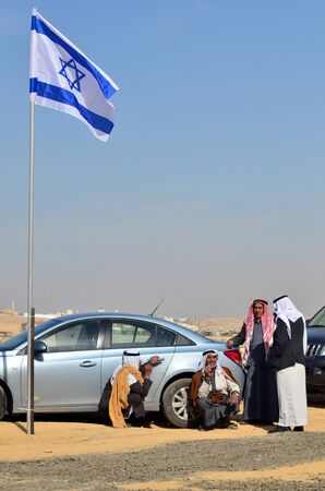 thobe: WESTERN NEGEV-DECEMBER 13:Bedouin arab men under the Israeli National flag near their bedouin village in southern Israel on December 13 2011.Negev Bedouin are formerly nomadic and later also semi-nomadic Arabs who live by rearing livestock in the deserts