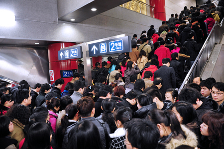 exits: BEIJING - MARCH 14:Big crowd exits Beijing subway during rush hour on March 14 2009 in Beijing,China.Its transports about 7 million people every day, which is about the total population of Cairo