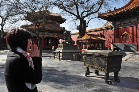 people's cultural palace: BEIJING - MAR -13: Buddhist Tibetan woman is praying and worship at the Lama Temple on March 13 in Beijing, China.Its one of the largest and most important Tibetan Buddhist monasteries in the world. Editorial