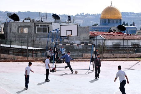 disputed: JERUSALEM - NOV 12: Arab men play football against the Golden Dome Mosque on November 08 2008 in Jerusalem, Israel.Its the most disputed holy ground between Muslims and Jewish people.
