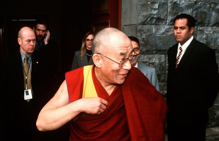 AUCKLAND, NEW ZEALAND - APRIL 10 2003: His Holiness the 14th Dalai Lama of Tibet is surrounding by bodygourdS while visiting in New Zealand in 2003.He has lived in exile in India since the Chinese Army crushed an uprising in his homeland in 1959.