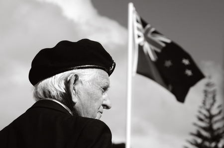 cross armed: MANGONUI, NEW ZEALAND - APRIL 25 2012: NZ veteran soldier stands under New Zealand flag at the National War Memorial on April 25 2012 in Mangonui, New Zealand BW Editorial