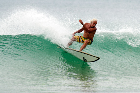 HENDERSON BAY - JAN 20: An old man wave surfing in Henderson Bay on January 20 2013.It's a beach break on a sandy beach on the Aupouri Peninsula, at the very top of the North Island in New Zealand. Редакционное