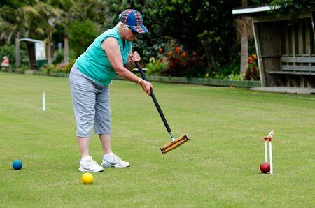 allowing: TAIPA  - NOVEMBER 28: Croquet player plays Croquet in Taipa club in Northland, New Zealand on November 28, 2012. Croquet was the first outdoor sport to embrace equality, allowing both sexes to play the game on an equal footing.