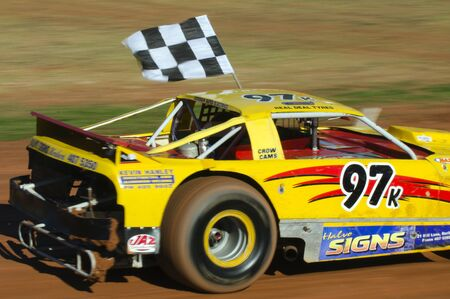 TAIPA, NEW ZEALAND - JUNE 02 2012:A winner of a super stock cars category carry a checkered flag during a dirt track racing on June 02 2012 in Taipa speedway, New Zealand.