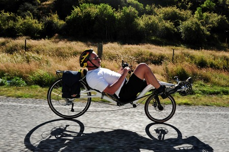 transportaion: WANAKA, NZ - MAR 02:Biker ride Recumbent bicycle on Mar 02 2009 near Wanaka, NZ.It holds the world speed record for a bicycle and they were banned from racing under the UCI in 1934 and now race under the banner of the Human Powered Vehicle Association HPV