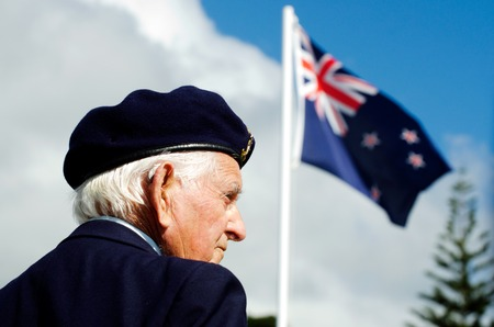 cross armed: MANGONUI, NEW ZEALAND - APRIL 25 2012: NZ veteran soldier stands under New Zealand flag at the National War Memorial on April 25 2012 in Mangonui, New Zealand Editorial