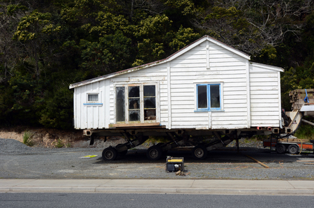 shifting: MANGONUE, NZ - OCT 05:Transporting an old house to a new location on Oct 05 2013.The cost of buying an old house for removal can range from a few thousand dollars to over 100,000 for a large home.