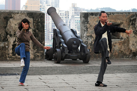 taichi: MACAU - FEB 20:Chinese couple practice Tai Chi on Guia Hill  Guia Fortress on February 20 2009 in Macau, China.The fort was built by the Portuguese empire in 1865 designed to defend Macau city. Editorial