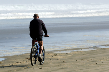 rides: A man rides a bike over Ninety Mile Beach in Northland New Zealand.