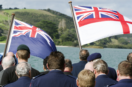 cross armed: The national flags of England and New Zealand In a National War Memorial during Anzac Day Services in New Zealand.