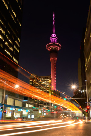 new automobile: Motion traffic light trail of vehicles in Auckland CBD in the foreground with the Sky Tower in the background at dusk. Vertical Stock Photo