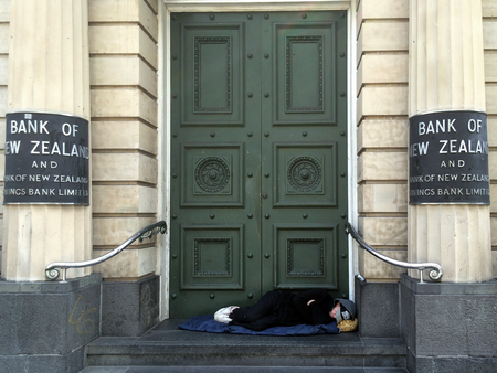 poverty: AUCKLAND,  NZL - OCT 05 2015:Homeless sleep under the doorway of New Zealand Bank in Auckland. In 2104 Statistics New Zealand estimated about one in 120 New Zealanders were homeless or housing