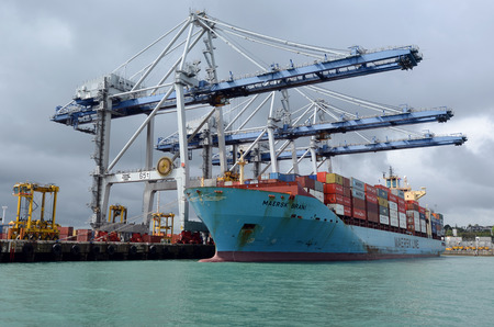 unloading: AUCKLAND,  NZL - OCT 13 2015:Big cargo ship unloading containers in Ports of Auckland New Zealand.It's New Zealands busiest port and the third largest container terminal in Australasia. Editorial