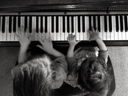 2 人の子供 (05、2 歳の女の子) は、ピアノで音楽を再生します。空中の視点 写真素材 - 47252920