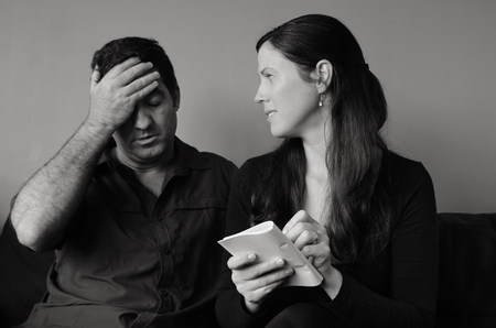 the spouse: Worried husband and wife  listing expenses in the living room. Spouse relationship concept (BW)