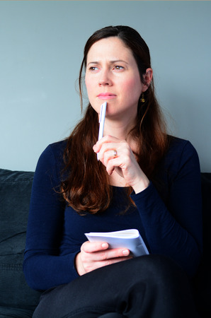 thirties: Young woman in her thirties (30s) hold a notepad thinking about to do list at home