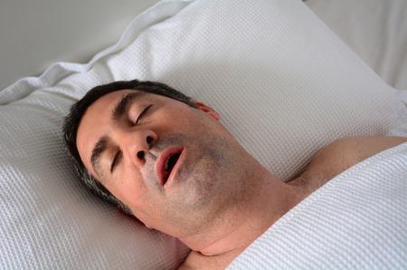 visage homme: Homme dans la quarantaine (40s) le ronflement dans le lit. concept de soins de sant�