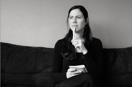 Young woman in her thirties (30s) hold a notepad thinking about to do list at home (BW) horizontal Stock Photo