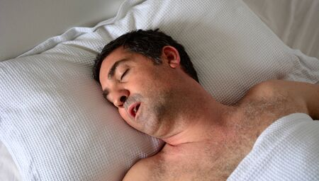 forties: Man in his forties (40s) snoring in bed. Health care concept