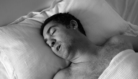 forties: Man in his forties (40s) snoring in bed. Health care concept (BW)