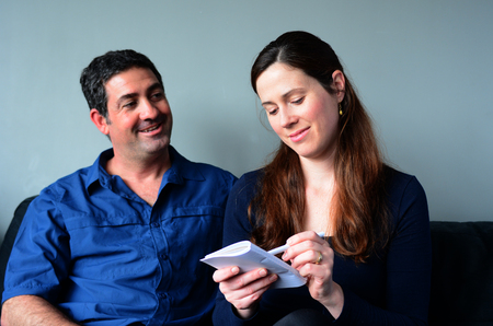 the spouse: Happy couple filling shopping list and smiling at home. Spouse relationship concept