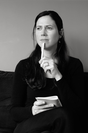thirties: Young woman in her thirties (30s) hold a notepad thinking about to do list at home (BW) vertical Stock Photo