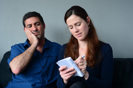 financial planning married: Worried couple listing expenses in the living room. Money and relationship  concept Stock Photo