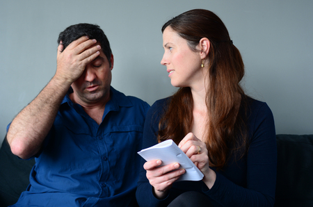 the spouse: Worried husband and wife  listing expenses in the living room. Spouse relationship concept