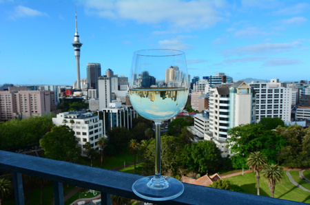 sauvignon blanc: Selective focus of a white wine, Sauvignon Blanc, glass against Auckland skyline, New Zealand.