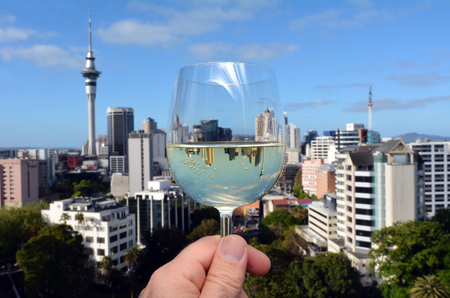 sauvignon: Mans hand holds a white wine, Sauvignon Blanc glass, against Auckland skyline, New Zealand.