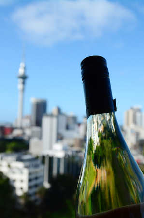 sauvignon blanc: Selective focus of a White wine, Sauvignon Blanc, bottle against Auckland skyline, New Zealand. Stock Photo