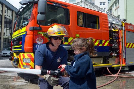 incendio casa: AUCKLAND - 27 de octubre de 2015: Bombero y niño Talya Ben-Ari 05 años de edad durante la educación de seguridad contra incendios day.Each año más de 20.000 incendios son atendidos por Nueva Zelanda Servicio de Bomberos con cerca de 5.000 incendios en el hogar.