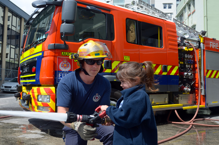 AUCKLAND  - OCT 27 2015:Firefighter and child Talya Ben-Ari age 05 during Fire Safety Education day.Each year over 20,000 fires are attended by New Zealand Fire Service with about 5,000 house fires.