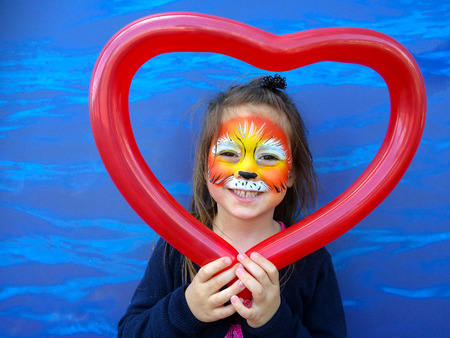 face painting: Little child (girl age 5-6)  with lion face painting  holding balloon in a shape of heart
