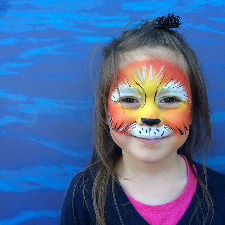 face painting: Little child (girl age 5-6) with lion face painting roaring like a lion.