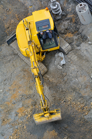 excavating: Aerial view of excavator digger digging and excavating foundation in construction site Stock Photo