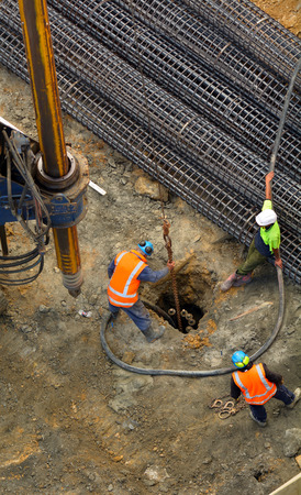 earthmover: Aerial view of unrecognizable workers with hydraulic hammer drilling machine creating foundation at Construction Site
