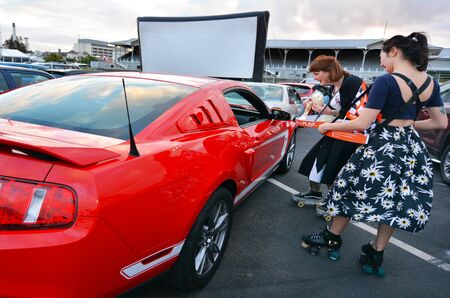 AUCKLAND - NOV 01 2015:Roller-skate waiters sale popcorn in Drive-in theater. Today there is only 400 drive-ins in the United States and another 100 exist around the world mainly in Canada and Australia.