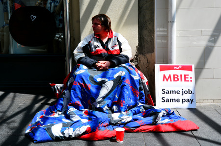 a situation alone: AUCKLAND,  NZL - NOV 05 2015:Homeless begging for money in Auckland New Zealand.In 2104 Statistics New Zealand estimated about one in 120 New Zealanders were homeless or housing deprived.