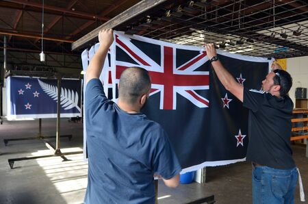 silver fern: AUCKLAND - NOV 24 2015: Workers hang a print of the National New Zealand flag. Between 20 Nov and 11 Dec New Zealanders will consider options to their National Flag future.