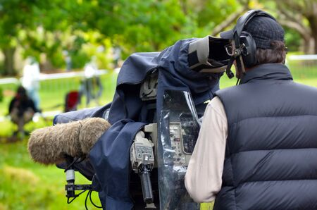 camera operator: AUCKLAND,  NZL - NOV 22 2015: Camera operator shooting on location event. In 2006, there were approximately 27,000 television, video, and motion picture camera operators employed in the United States.