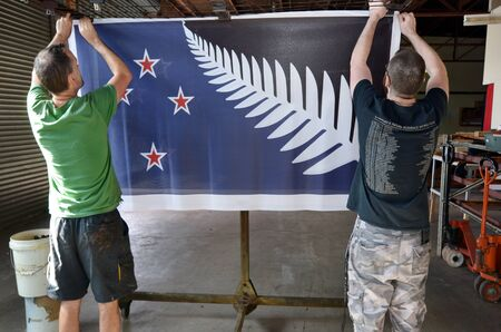 silver fern: AUCKLAND - NOV 24 2015: Workers hang aprint of the Silver Fern (Black, White and Blue) flag. Between 20 Nov and 11 Dec New Zealanders will consider options to their National Flag future. Editorial