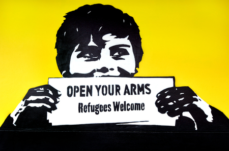 accepts: AUCKLAND, NZL - NOV 20 2015: Graffiti with the political slogan Refugees Welcome.Each year New Zealand accepts 750 refugees as agreement with the United Nations High Commissioner for Refugees.