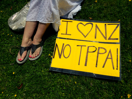 new economy: AUCKLAND - NOV 14 2015:New Zealand Woman protester with her opinion on a sign in Anti-TPPA Rally.12 nations including New Zealand negotiating TTP trade deal, which would cover 40% of the world economy Editorial
