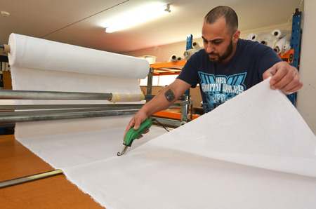 silver fern: AUCKLAND - NOV 24 2015: Worker cut new fabric sheet for the new National flag of New Zealand. Between 20 Nov and 11 Dec New Zealanders will consider options to their National Flag future
