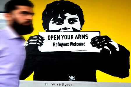 accepts: AUCKLAND - NOV 20 2015:Middle eastern man pass by Graffiti reads: Refugees Welcome.Each year New Zealand accepts 750 refugees as agreement with the United Nations High Commissioner for Refugees.